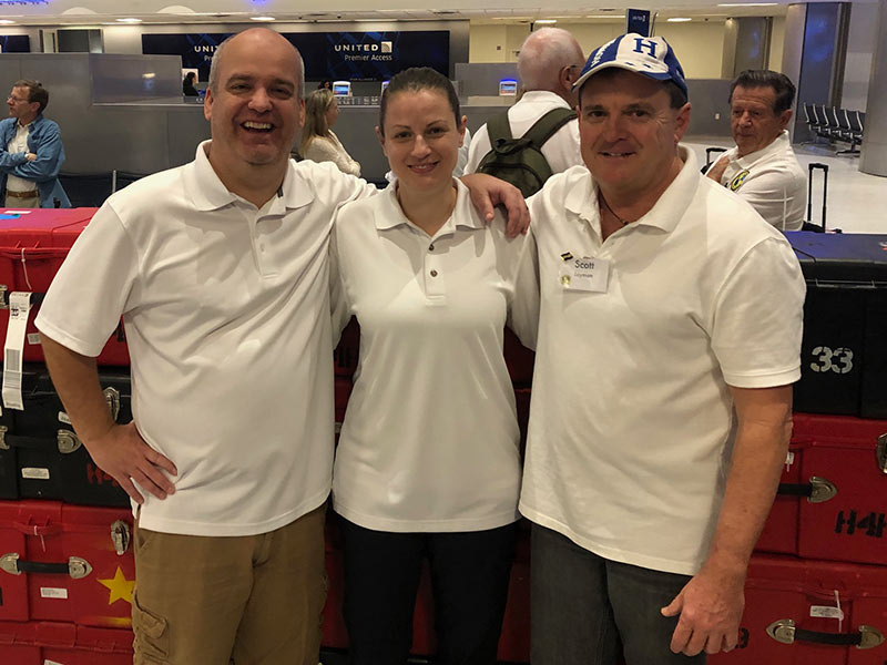 Two men and a woman in white shirts stand with arms around each other smiling at the airport in front of stacks of cases.