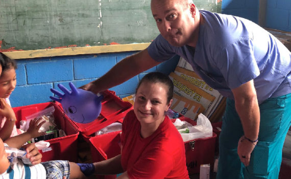 Man and woman bending down surrounded by boxes of medical supplies. They are looking up at the camera and smiling.