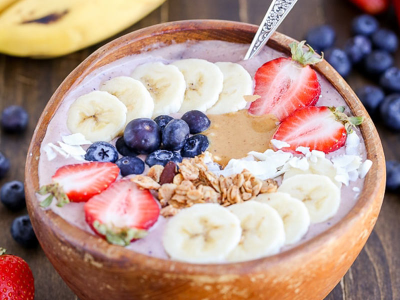 Acai bowl topped with sliced bananas and strawberries, blueberries, granola and a dollop of peanut butter.