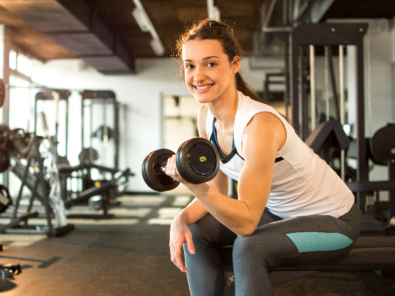 Woman sitting on weight bench in gym clothes leaning forward with a weight in her arm, pumping the weight and smiling.