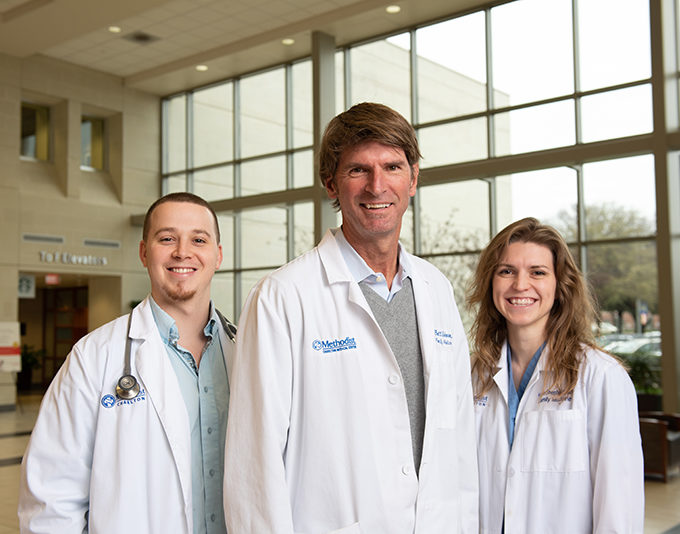 Three doctors, two men and one woman, stand in the hospital atrium wearing white coats, one has a stethoscope.