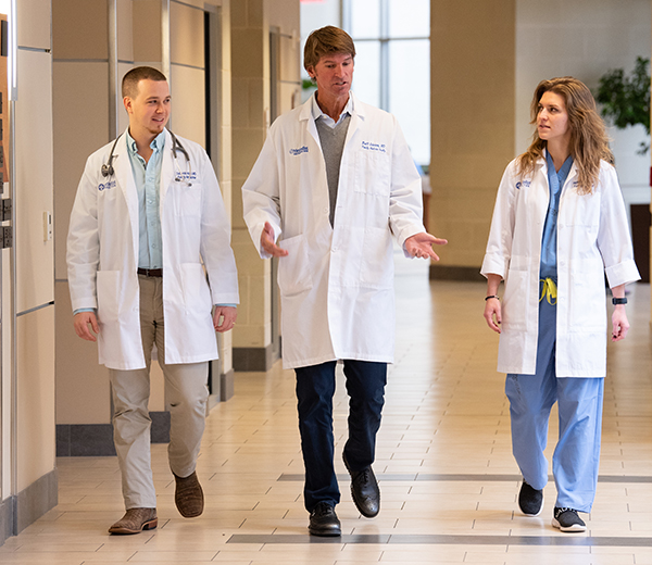 Three doctors walk down a hospital hallway wearing white lab coats. The middle doctor talks and the other two look at him.