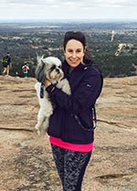Woman in exercise clothes standing on top of a mountain holding a dog