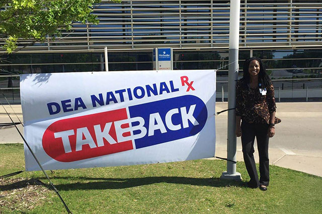 Woman standing outside leaning on a pole next to a sign that reads DEA National RX Take Back.