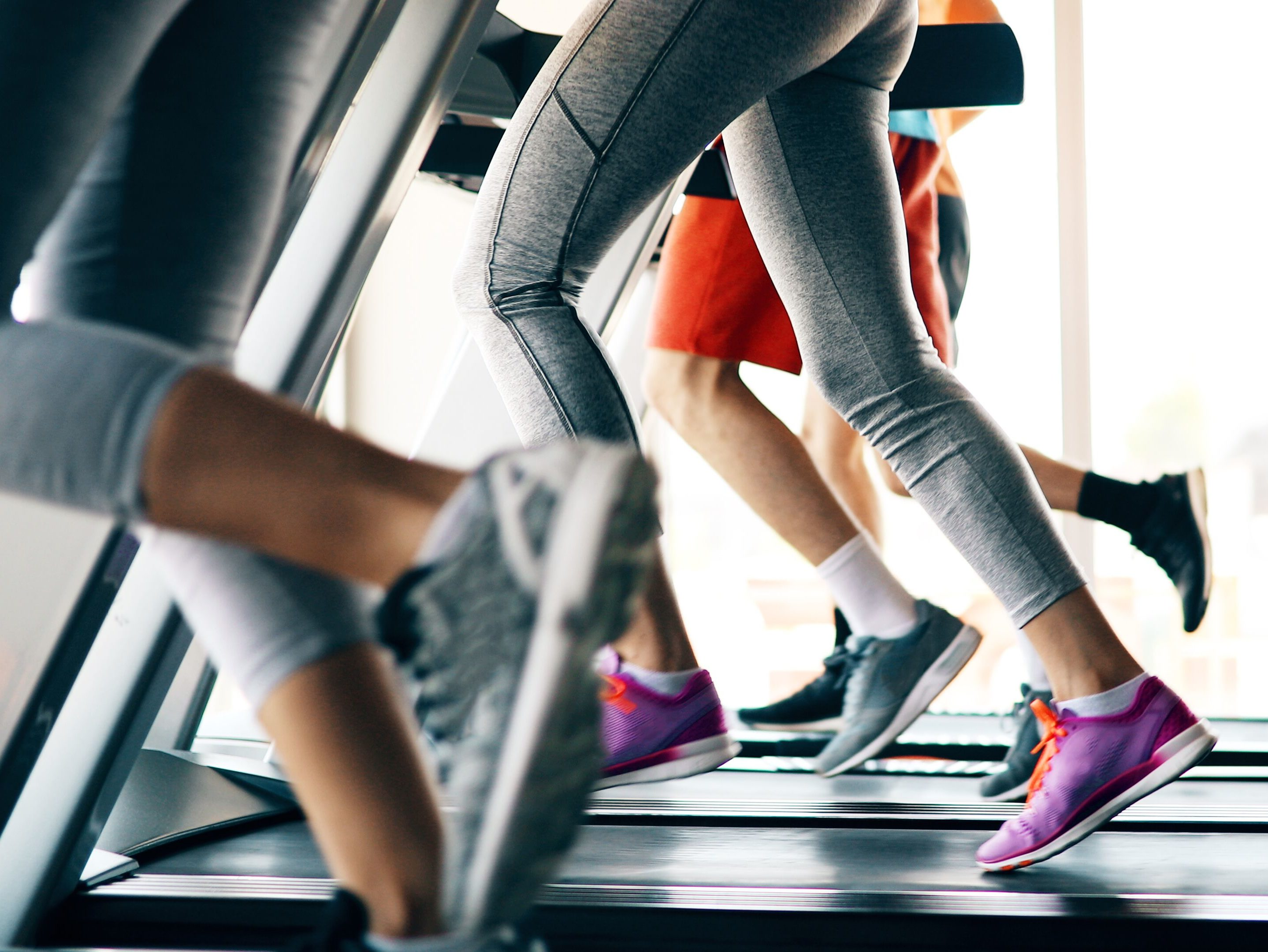 Row of treadmills seen from users' waist down. All have runners using treadmills in exercise gear and tennis shoes.