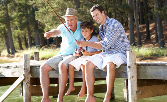Son, dad and grandfather sit on a dock, legs dangling. The youngest is fishing with a pole, the older men are helping.