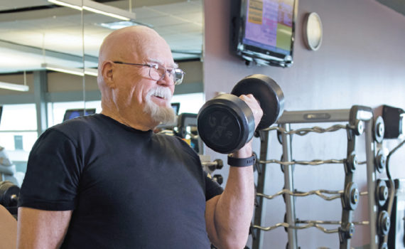 Man wearing blue shirt and glasses with mustache and no hair in weight room, lifting weight with one arm.