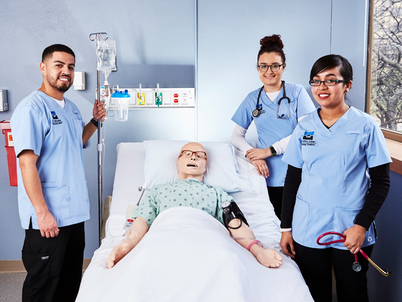 Three nursing students in scrubs stand around a hospital bed with a mannequin in it.