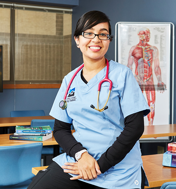 Nurse sitting on desk in scrubs with stethoscope around her neck. Poster of human muscles is in the background.