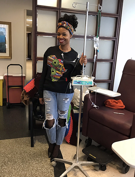 Woman standing in hospital waiting room in a sweatshirt, ripped jeans, heels and a head wrap holding an IV stand.