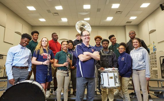 Skip Redd in music room surrounded by students with musical instruments.