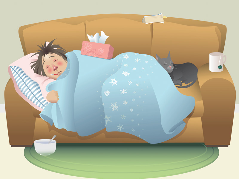 Person lying under a blanket on a couch with a box of tissues on top, a thermometer in mouth, a book, a tea mug and a cat.