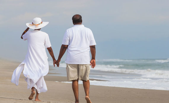 Man and woman holding hands on a beach wearing white and walking away. Woman is wearing a white sun hat.