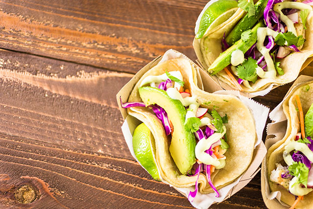 Three sets of tacos filled with avocado and cabbage and cilantro sit on a brown wooden table.