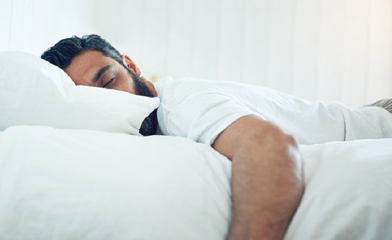 Man with dark hair and beard asleep on a bed with white sheets and pillow cases. His arm is dangling off the side of the bed.