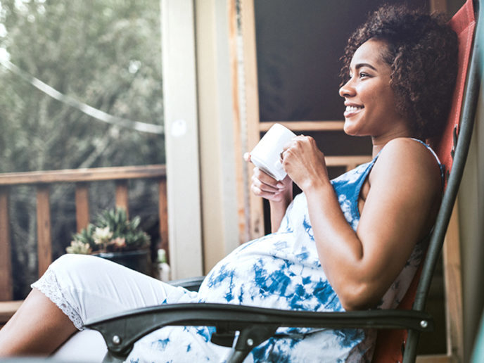 Pregnant woman sitting in rocking chair on a porch with a mug in her hand.