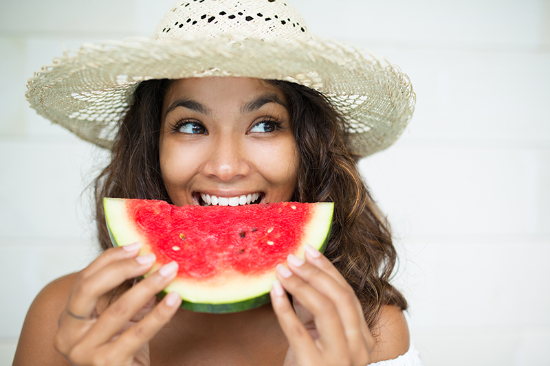 Woman with brown hair wearing straw hat eating a half-moon slice of watermelon.