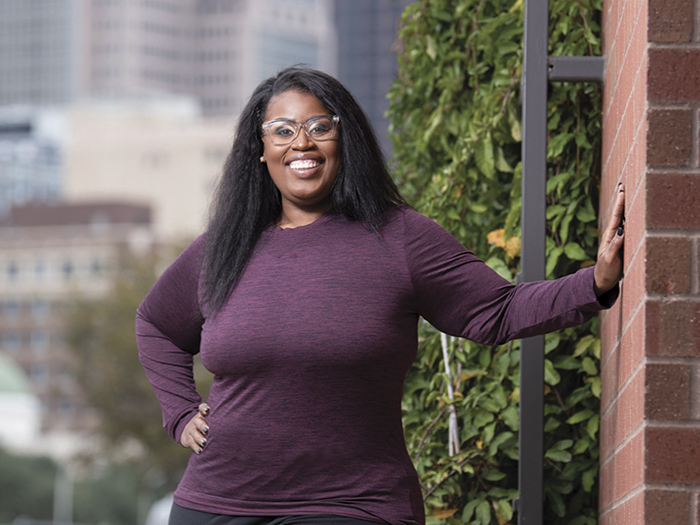 Woman with glasses standing and smiling with hand on hip leaning on a wall with ivy with city background.