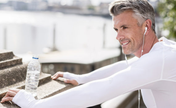 Man stretching in exercise clothes and water bottle