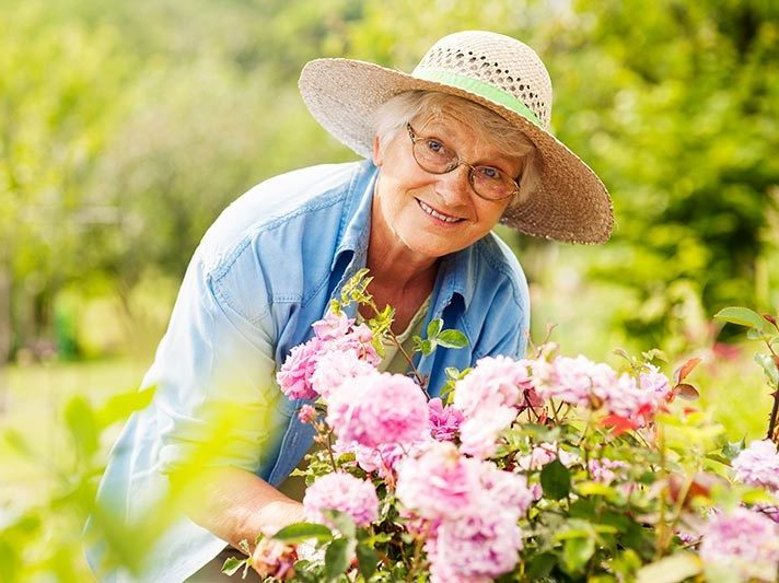 Older woman in straw hat is bent over flower bed outside.