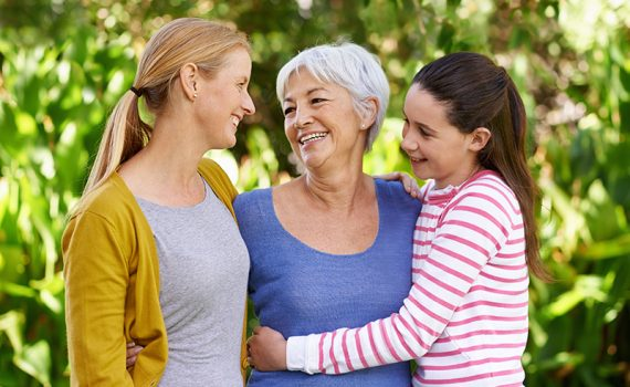 Three women from three generations stand outside with arms wrapped around each other.