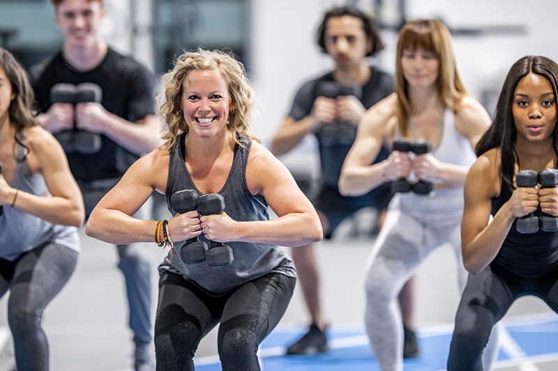 Woman in gym class with other participants all holding weights