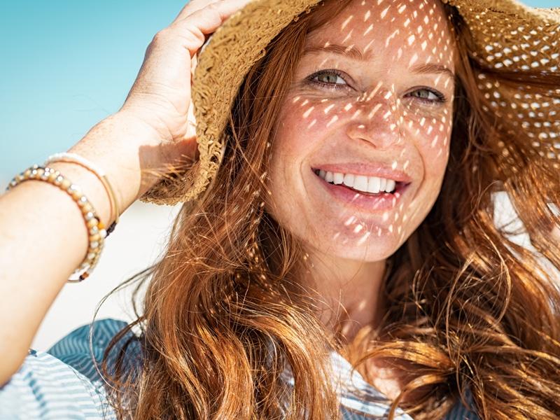 Woman smiling outside wearing hat to avoid heat stroke or heat exhaustion.