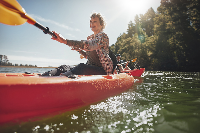 Middle - aged, heart - healthy woman paddling a red canoe on a sunny day