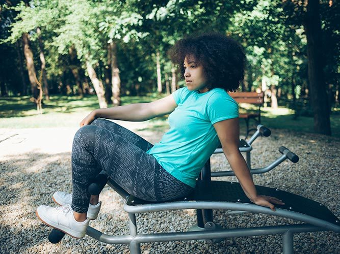 Young African - American woman sitting on sit - up bench in park