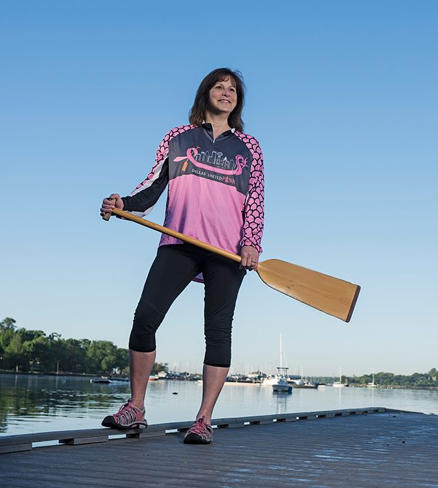Breast cancer survivor Kathy Bockman stands on dock with paddle for dragon boat racing.