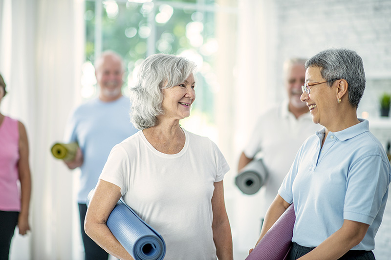 White middle-aged woman and an Asian middle-aged woman holding yoga mats talking after a tai chi class.