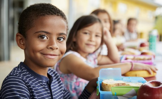 Young boy and girl at school lunch table smiling to camera.