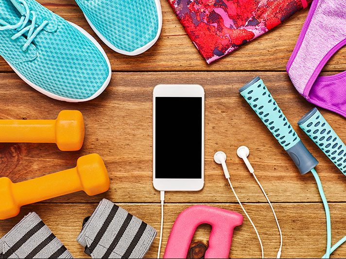 Smartphone with gym accessories and tennis shoes. Download a fitness app.