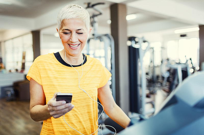 Mature Woman Exercising on treadmill in the gym and using smartphone fitness app.