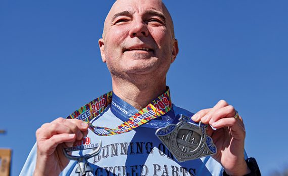 "Transplant patient Mike Barker wears Cowtown Half Marathon medals and shirt that says ""running on recycled parts."""
