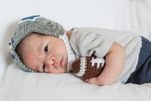 Baby in the NICU wears a crochet football helmet.