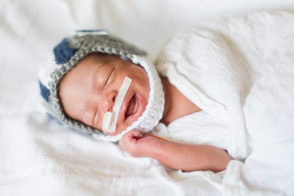 Baby in the NICU wears a crochet football helmet.