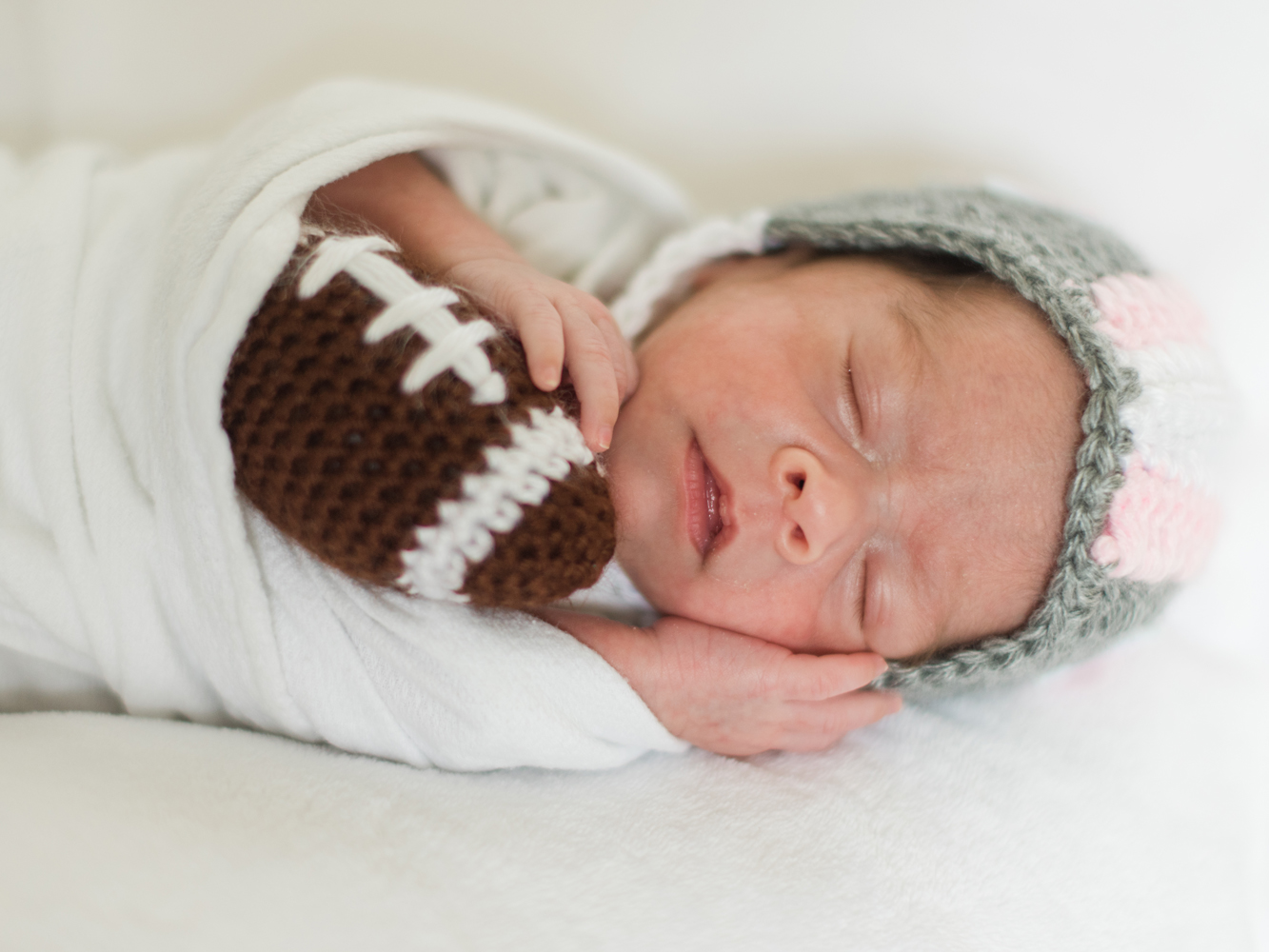 Baby in the NICU wearing a crochet football helmet.
