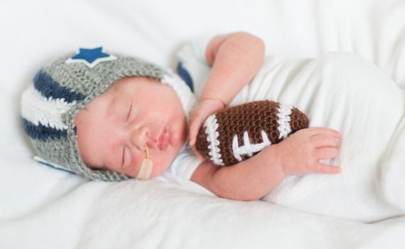 NICU baby wears a crochet football helmet.