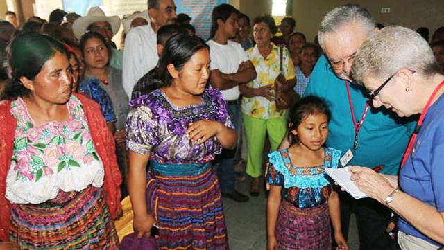 Two women and a young girl speak to volunteers for their health screenings during a surgical medical mission trip.