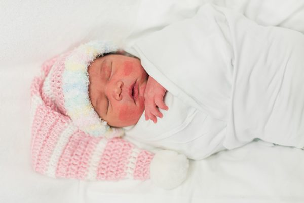 Baby in the NICU wears a crochet Christmas stocking hat.