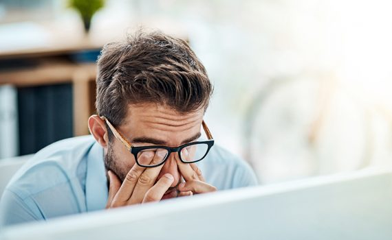 Man sitting at desk rubbing eyes indicating lack of work-life balance.