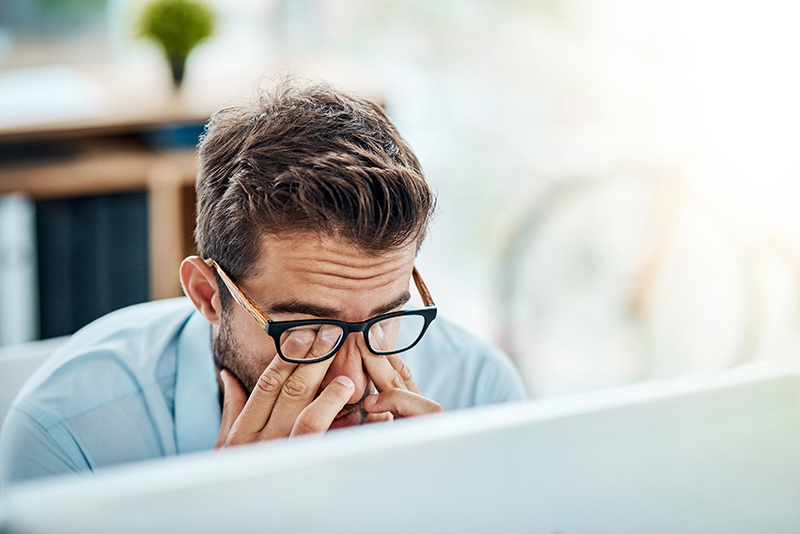 Man sitting at desk rubbing eyes indicating lack of work-life balance.