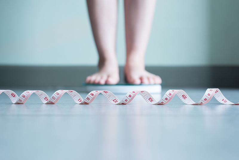 Feet standing on scale with measuring tape in foreground; person is considering weight-loss surgery.