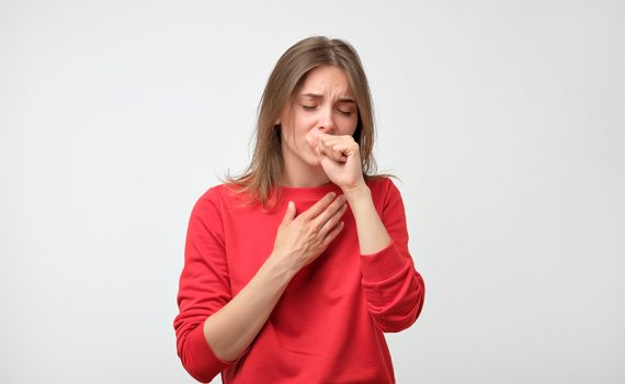 Woman holding chest and coughing; learn about cough care.