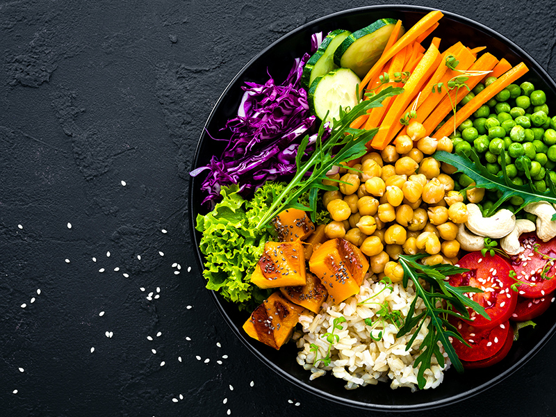 Large salad with fresh vegetables to think outside the takeout box for healthy lunches.