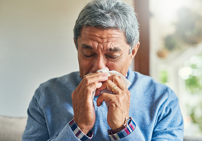 Older adult blowing his nose; flu vaccines can help lessen the risk of getting the flu.