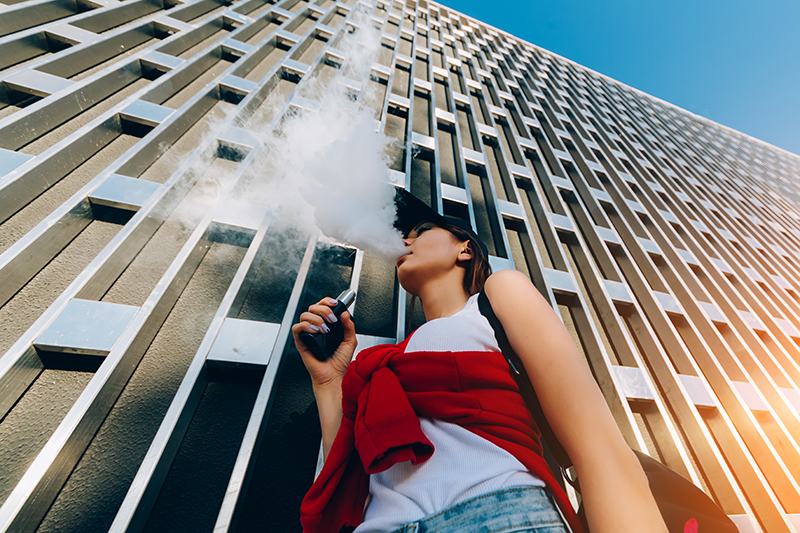 Woman outside a building vaping.