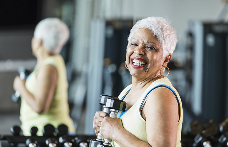 Woman exercising at gym with weights; conquer your fitness plateau with these tips.