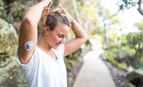 Woman outside in T-shirt with an insulin patch for managing diabetes on her arm.